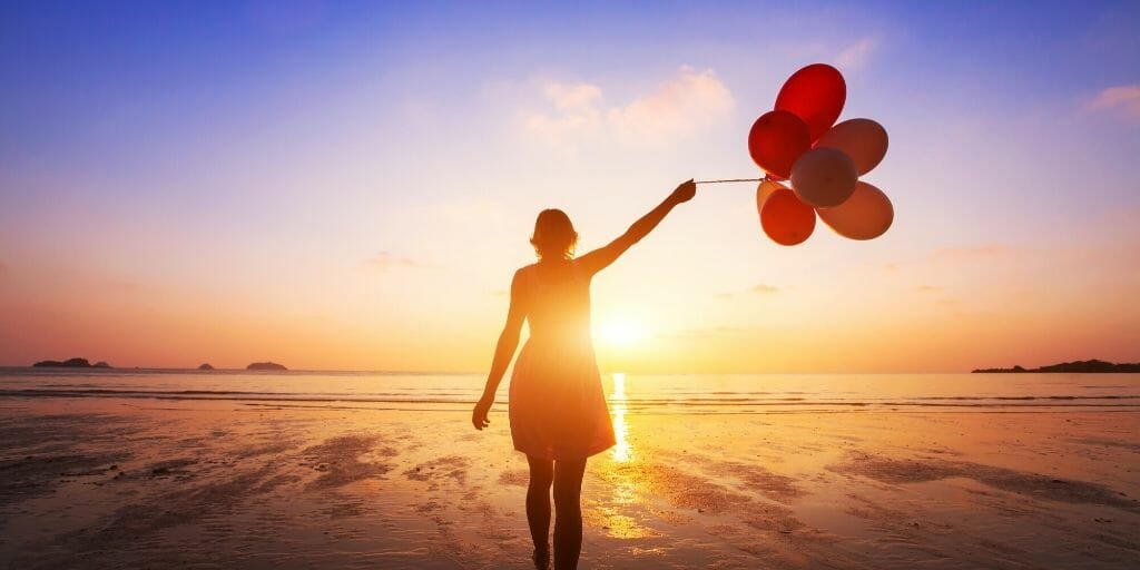 Woman on the beach holding balloons